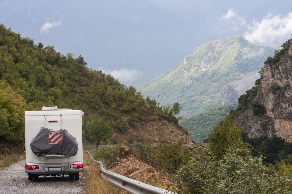 RV travelling on road among high mountains