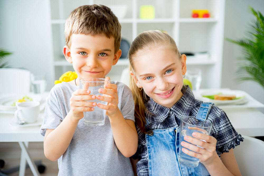 Kids holding a glass of water