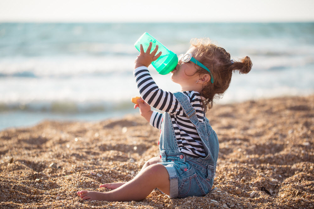 Little girl drinking water on the beach