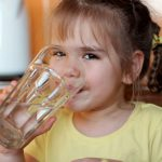A child drinks water in a glass