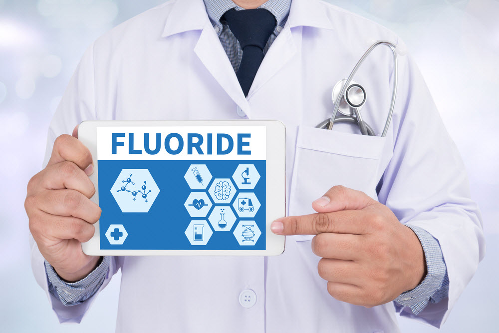 Doctor holding a tablet with a sign of Fluoride