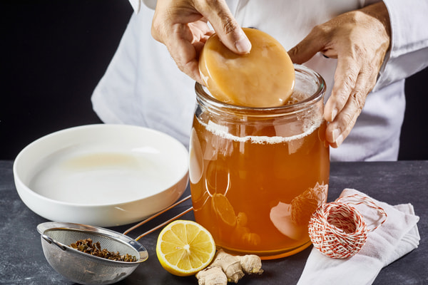 Man placing the scoby or fungus in a glass jar