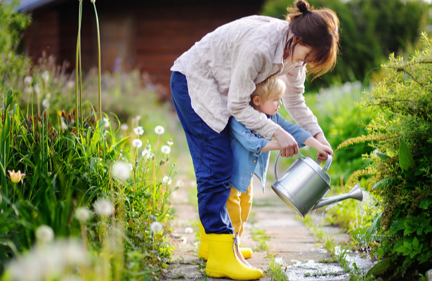 WFA - Toddler boy and his mother watering plants in the garden