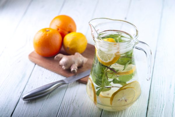 WFA - Glass jug with mineral water, lemon slices and mint leaves, ginger, lemon and oranges with knife on wooden table.