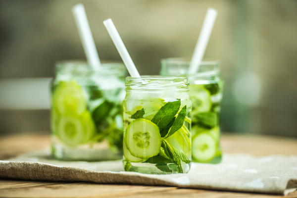 WFA - Three glass jars of lemonade with cucumber and mint on wooden table