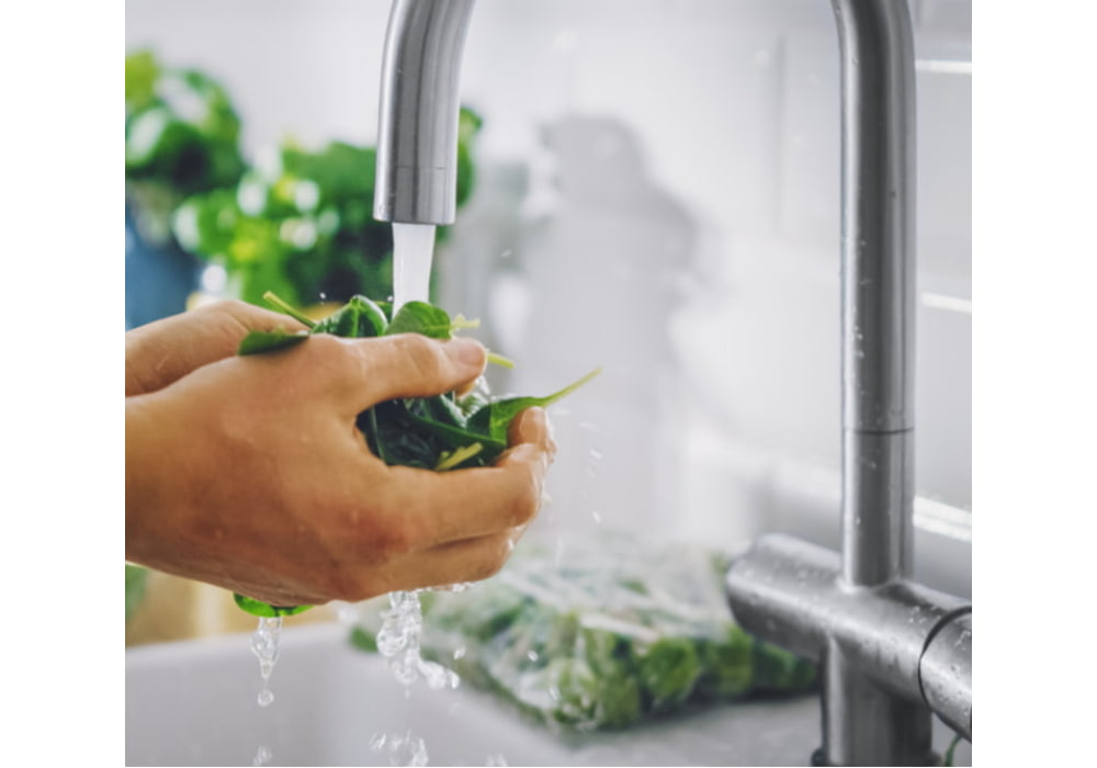 Man washing green spinach leaves with tap water