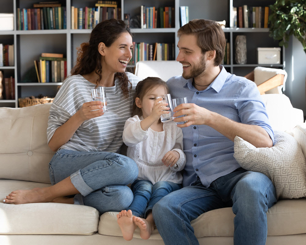 Happy family holding clean glass of water while sitting on a couch